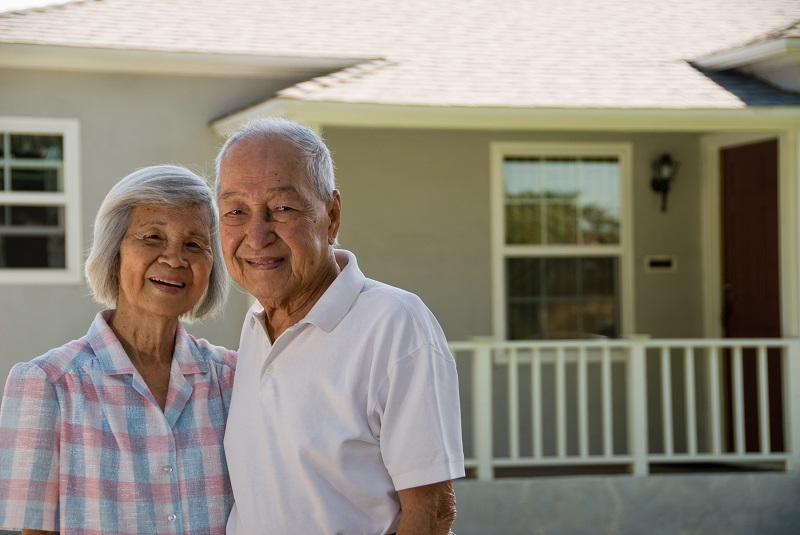 Grandma and Grandpa in front of house smiling at the camera.